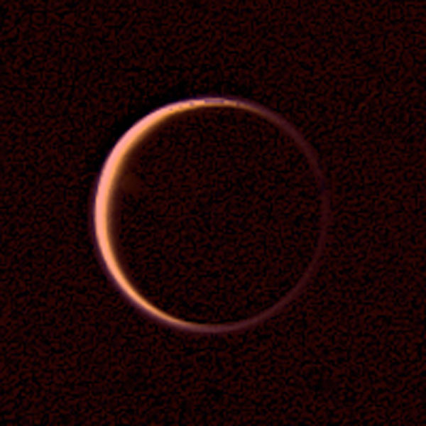 NASA's Voyager 2 obtained this wide-angle image of the night side of Titan on Aug. 25, 1979. This is a view of Titan's extended atmosphere. the bright orangish ring being caused by the atmosphere's scattering of the incident sunlight.