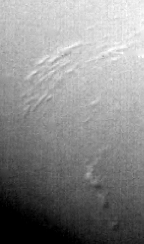 This image of Neptune's south polar region was obtained by NASA's Voyager on Aug. 23, 1989. The smallest cloud features are 45 kilometers (28 miles) in diameter. The image shows the discovery of shadows in Neptune's atmosphere, shadows cast onto a deep cl