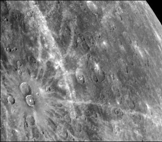 This photograph of Mercury, taken by NASA's Mariner 10, shows two prominent rayed craters. Bright halos extend as far as 2 crater diameters beyond crater rims. Individual rays extend from halo.
