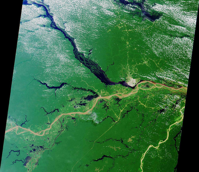 Close to the city of Manaus, Brazil the Rio Solimoes and the Rio Negro converge to form the Amazon River. This image from NASA's Terra satellite was acquired on July 23, 2000 during Terra orbit 3178.