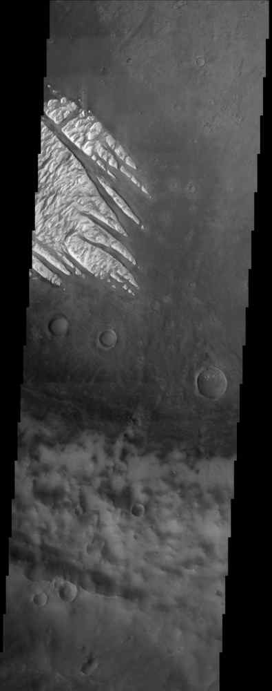 White Rock' is the unofficial name for this unusual landform which was first observed during NASA's Mariner 9 mission in the early 1970's and is now shown here in an image from NASA's Mars Odyssey spacecraft.