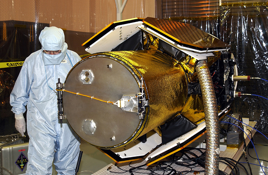 In the Multi-Payload Processing Facility, workers check the deployment of the cover of the telescope on NASA's Galaxy Evolution Explorer, an orbiting space telescope observing galaxies in ultraviolet light across 10 billion years of cosmic history.