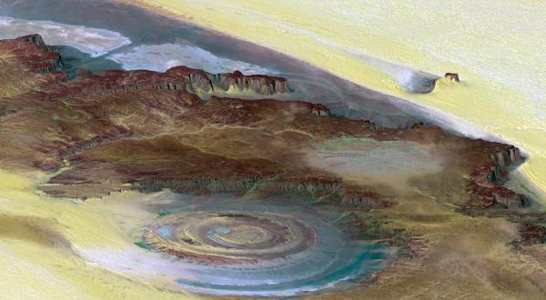 This prominent circular feature, known as the Richat Structure, in the Sahara desert of Mauritania is often noted by astronauts because it forms a conspicuous bull's-eye on the otherwise rather featureless expanse of the desert.