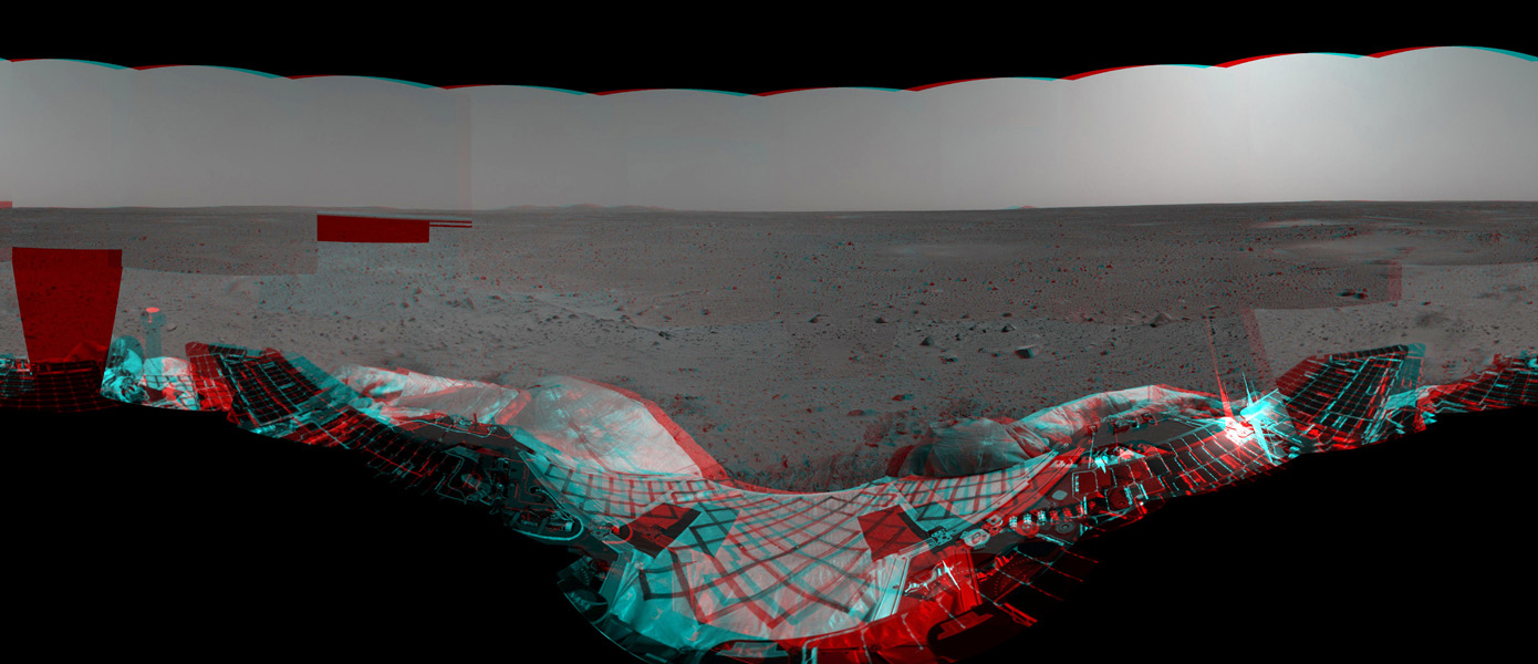 This anaglyph from NASA's Mars Exploration Rover, Spirit, shows the rover's lander and, in the background, the surrounding martian terrain. 3D glasses are necessary to view this image.