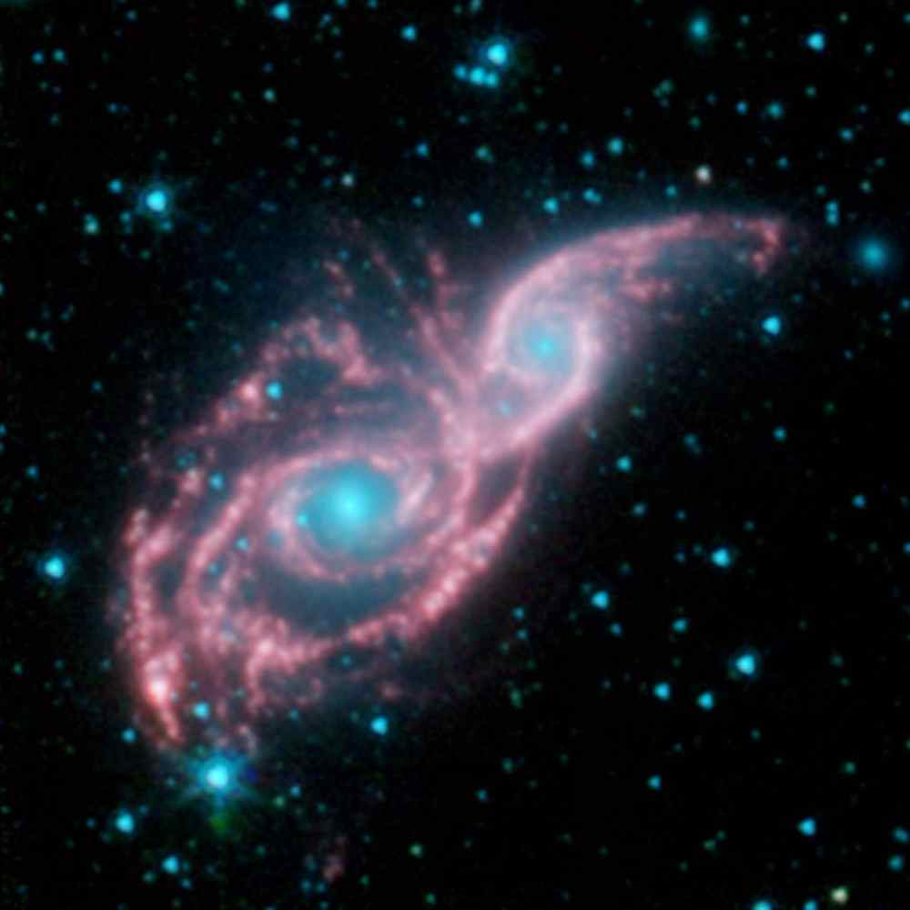 Something appears to be peering through a shiny red mask, in this new false-colored image from NASA's Spitzer Space Telescope. The mysterious blue eyes are actually starlight from the cores of two merging galaxies, called NGC 2207 and IC 2163.