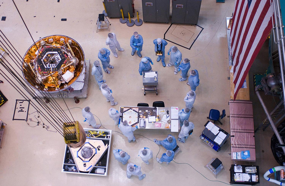 Spacecraft specialists huddle to discuss the critical lift of NASA's Phoenix Mars Lander into a thermal vacuum chamber