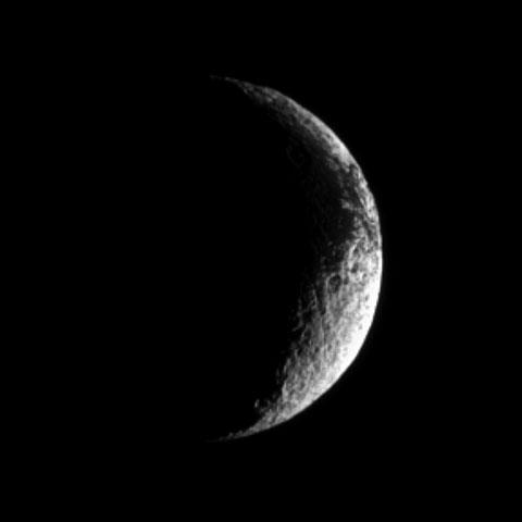 A crescent Iapetus shows, at the top right of this image from NASA's Cassini spacecraft, some of the dark terrain characterizing this unusual Saturnian moon.