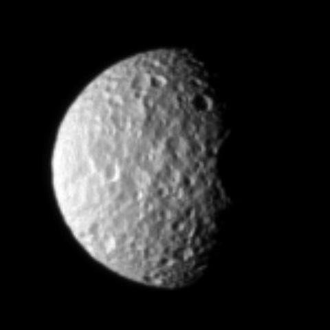 The oblate moon Mimas displays the cratered surface of its anti-Saturn side in this image taken by NASA's Cassini spacecraft.