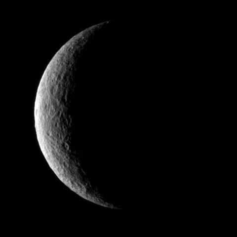 NASA's Cassini spacecraft captures a crescent of crater-covered surface on the moon Rhea. Lit terrain seen here is on the trailing hemisphere of Rhea. North on Rhea is up.