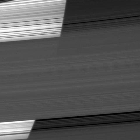 The limb of Saturn appears bright as NASA's Cassini spacecraft peers through several of the planet's rings. The curvature of the planet can be seen on the bright left half of the image.