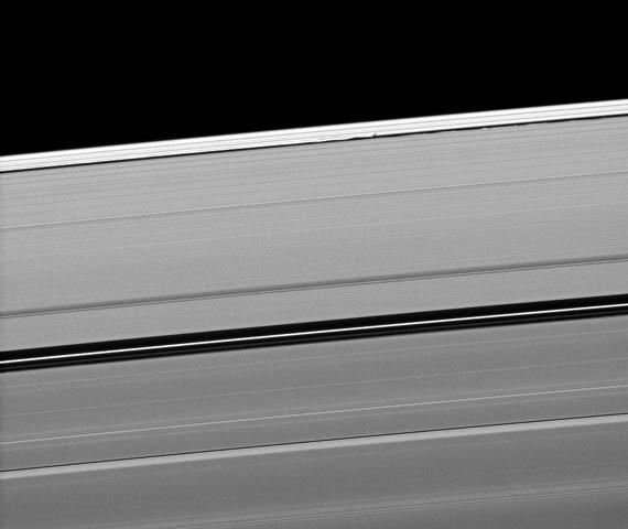 Saturn's moon Daphnis casts a short shadow on the A ring in this image taken by NASA's Cassini spacecraftabout six months after the planet's August 2009 equinox. Daphnis appears as a tiny bright dot in the Keeler Gap of the A ring near the center top.