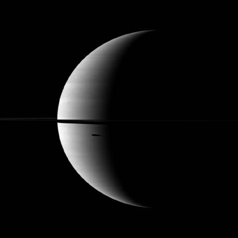 The shadow of Saturn's moon Dione, cast onto the planet, is elongated in dramatic fashion in this image captured by NASA's Cassini spacecraft. The moon itself does not appear here, but the shadow can be seen south of the ringplane.