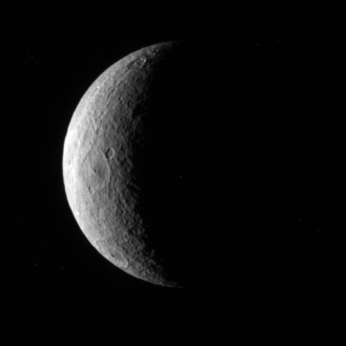 NASA's Cassini spacecraft pictures a crescent of Saturn's moon Rhea. Although craters dominate this particular view, the trailing hemisphere of Rhea also features wispy fractures.