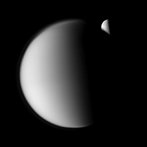 The moon Rhea moves behind Saturn's largest moon, Titan, in this 'mutual event' imaged by NASA's Cassini spacecraft. Part of Rhea's southern hemisphere is also visible here through the haze of Titan's atmosphere.