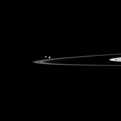 Two of Saturn's small moons can be seen orbiting beyond the planet's thin F ring in this image captured by NASA's Cassini spacecraft. Pandora is on the left, and Epimetheus is on the right.