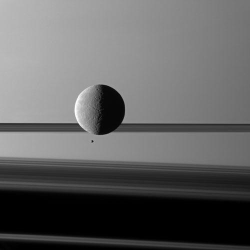 "Saturn's moon Rhea looms ""over"" a smaller and more distant Epimetheus against a striking background of planet and rings. The two moons aren't actually close to each other."