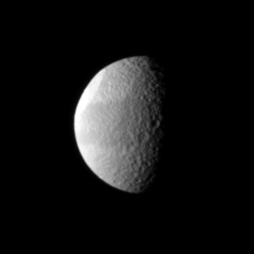 Tethys' huge Odysseus Crater is brightly lit in the northern latitudes of this Saturnian moon in this NASA Cassini spacecraft view. The crater is seen almost edge-on in the upper left of the image.