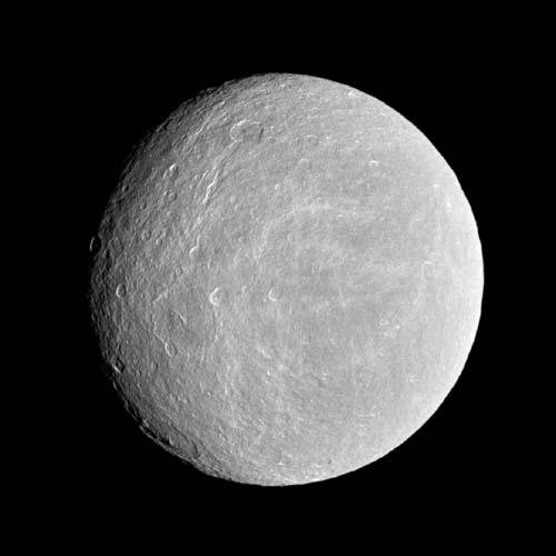 NASA's Cassini spacecraft looks toward the cratered plains of the trailing hemisphere of Rhea. Some of the moon's fractures, appearing like wispy bright lines, can be seen on the left of the image.