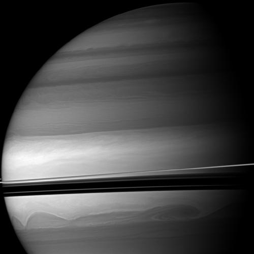Huge clouds swirl through the southern latitudes of Saturn where the rings cast dramatic shadows. This view from NASA's Cassini spacecraft looks toward the northern, sunlit side of the rings from just above the ringplane.