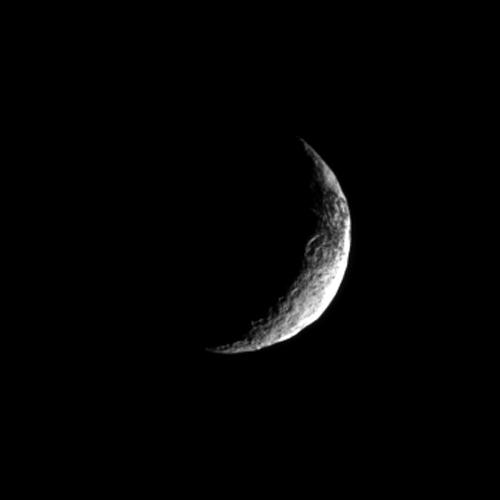 NASA's Cassini spacecraft looks toward a crescent of Saturn's moon Iapetus and glimpses a bit of that moon's yin-yang appearance.