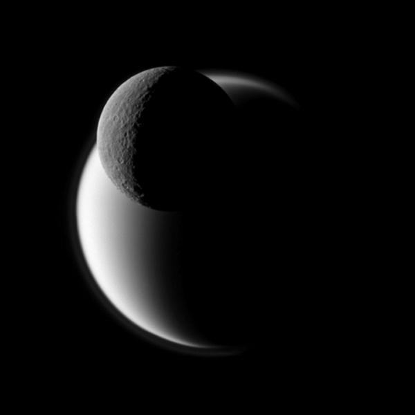 A darkly defined Rhea passes before the fuzzy orb of Titan in this view from NASA's Cassini spacecraft of Saturn's two largest moons. Rhea is closer to the spacecraft in this view.