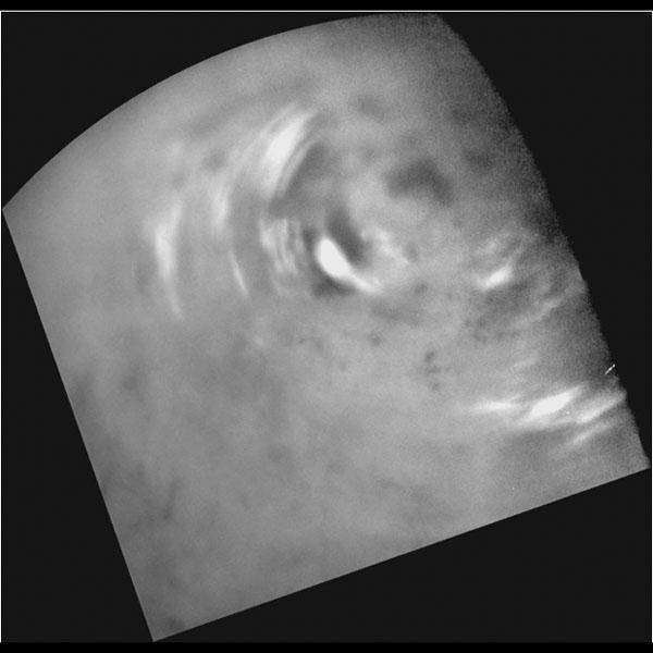 Clouds move above Titan's large methane lakes and seas near the moon's north pole in this image from NASA's Cassini spacecraft. Methane clouds in the troposphere, the lowest part of the atmosphere, appear white here.