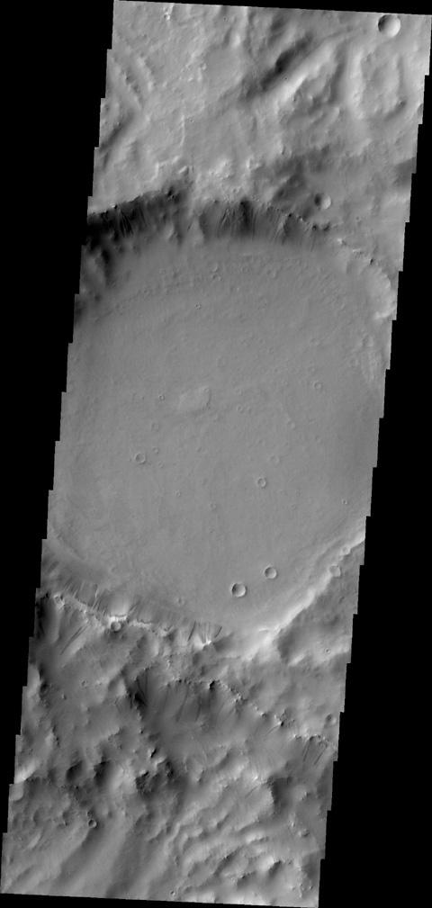 Gravity has caused materials to move down the rim of this crater in Terra Sabaea. In this image from NASA's 2001 Mars Odyssey, thinner dark slope streaks are less common than broader, lighter markings of downslope movement of materials.