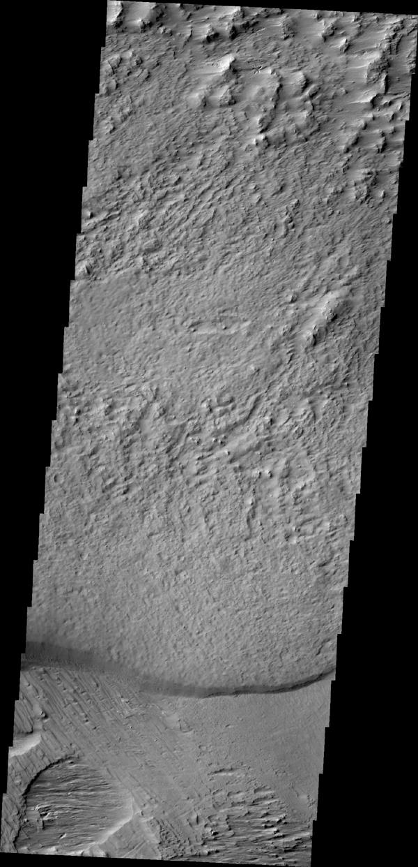 The region southwest of Olympus Mons is covered with materials that have been eroded by the wind. Surface materials in this area indicate wind action in many different directions as shown in this image from NASA's Mars Odyssey.