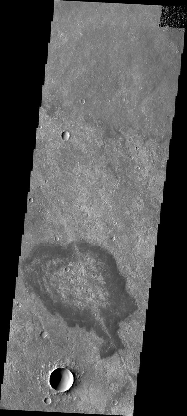 Located in Solis Planum, this unusual volcanic flow has margins darker than the surroundings. It appears that the flow originated in the linear fracture or vent that bisects the flow deposit. This image was captured by NASA's Mars Odyssey.