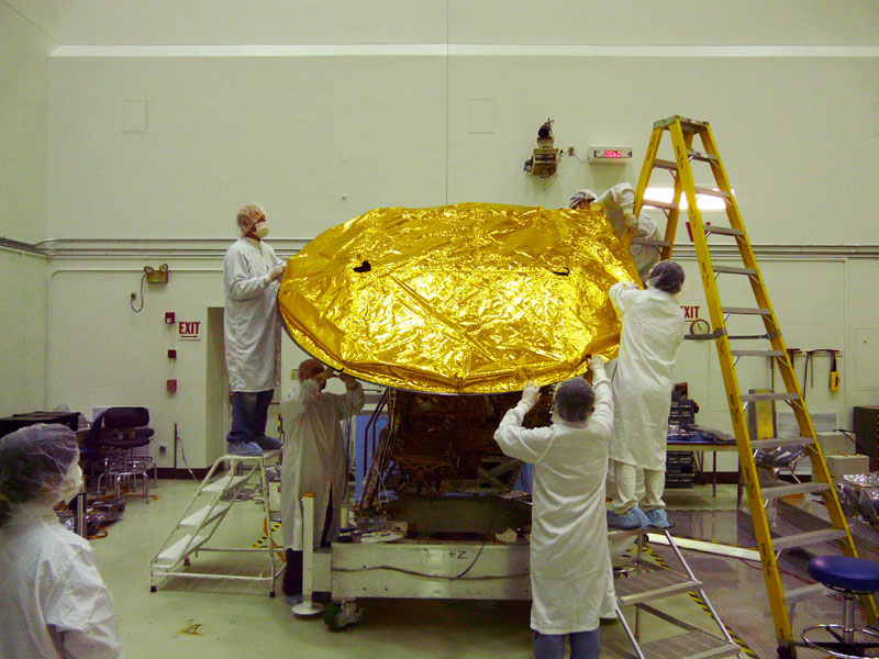 Aquarius 2.5 meter composite reflector being fitted with gold foil covering in the clean room at NASA's Jet Propulsion Laboratory in Pasadena, Calif.