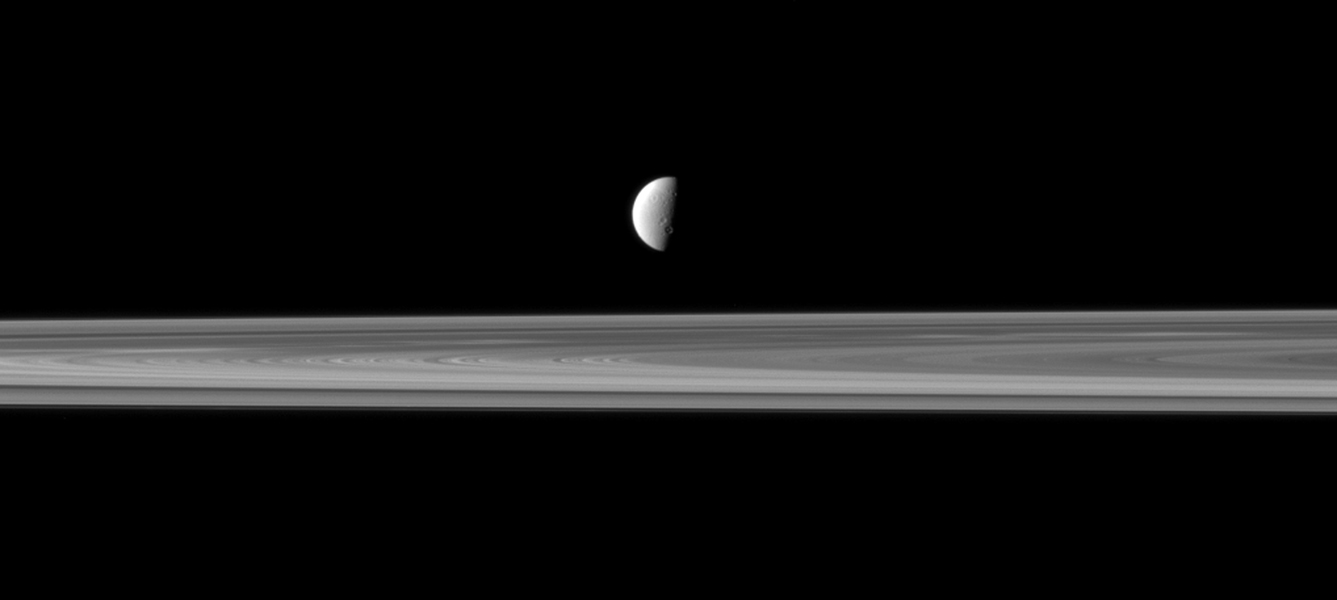 Saturn's fourth largest moon, Dione, appears like a solitary ornament suspended above the rings in view from NASA's Cassini spacecraft. The rings are closer to Cassini in this view, with Dione more distant.