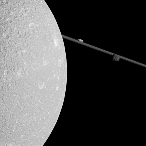 Flying past Saturn's moon Dione, NASA's Cassini captured this view which includes two smaller moons, Epimetheus and Prometheus, near the planet's rings.