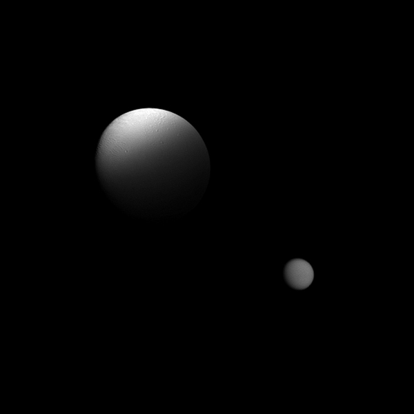 Saturn's moon Enceladus is partially eclipsed by the planet in this view from NASA's Cassini spacecraft which also features the moon Titan in the distance.