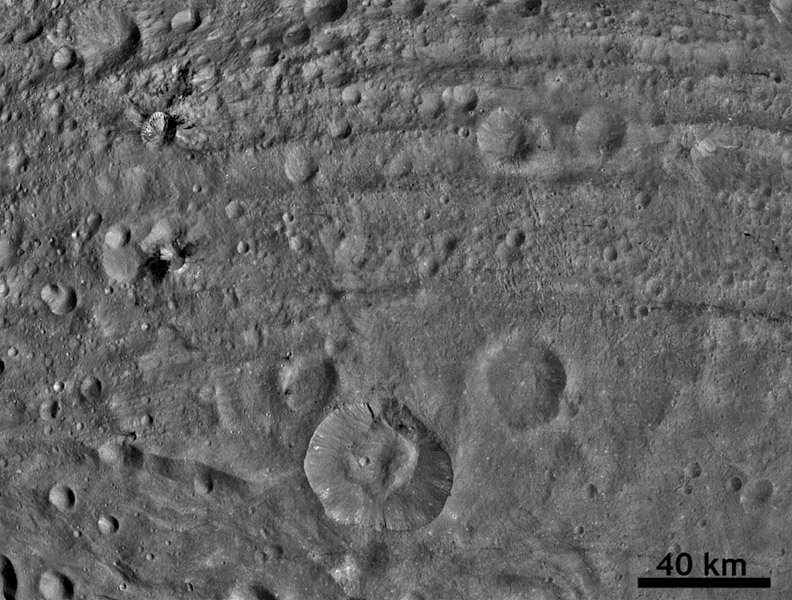 This image from NASA's Dawn spacecraft shows dark material at impact craters, up to 12.5 miles-wide (20 kilometer-wide) and sets of worm-like tracks in the north-south direction.
