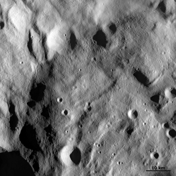 This image from NASA's Dawn spacecraft shows a raised mound material overlying the brighter material that makes up the floor of the south polar depression of asteroid Vesta. Many small scale craters are clear in this image.