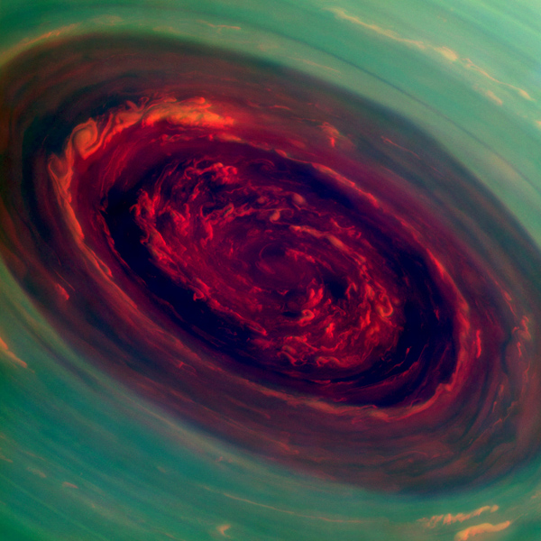 The spinning vortex of Saturn's north polar storm resembles a deep red rose of giant proportions surrounded by green foliage in this false-color image from NASA's Cassini spacecraft.