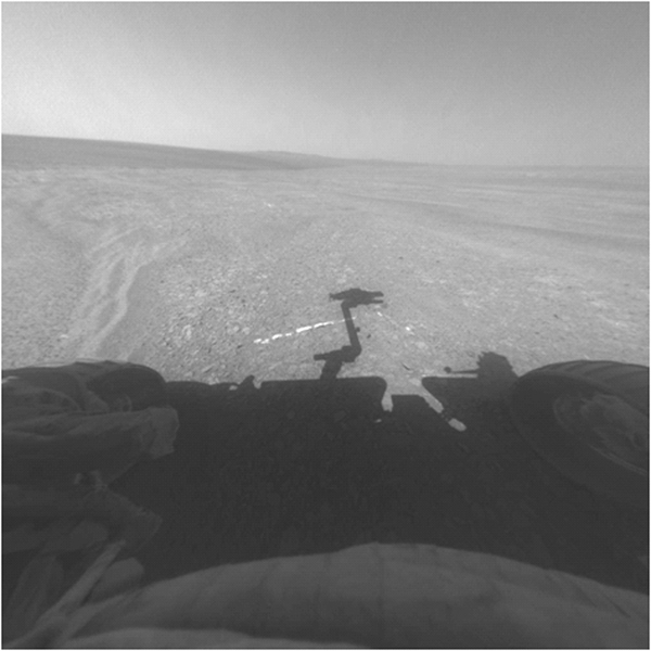 "This view from the front hazard-avoidance camera on NASA's Mars Exploration Rover Opportunity shows the rover's arm's shadow falling near a bright mineral vein informally named ""Homestake."""