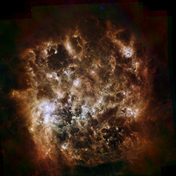 This image shows the Large Magellanic Cloud galaxy in infrared light as seen by ESA's Herschel Space Observatory and NASA's Spitzer Space Telescope. The brightest center-left region is called 30 Doradus, or the Tarantula Nebula.