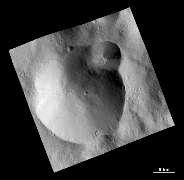 This image from NASA's Dawn spacecraft shows a large crater with several smaller craters at the edge on the giant asteroid Vesta. Rough texture in the crater wall at far right may be the underlying bedrock.