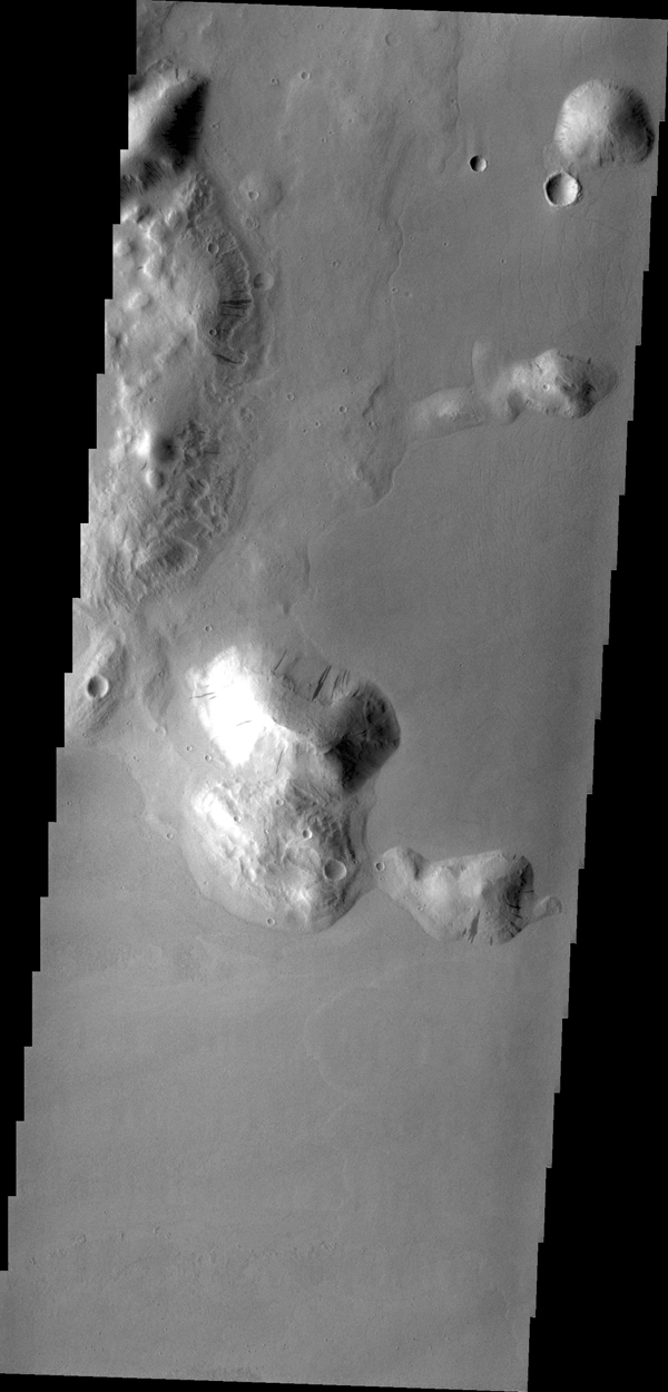 Dark streaks mark the sides of this mesa where the movement of material has exposed the darker rock beneath. This mesa (or hill) is just one of hundreds in Tartarus Colles. This image was captured by NASA's 2001 Mars Odyssey spacecraft.