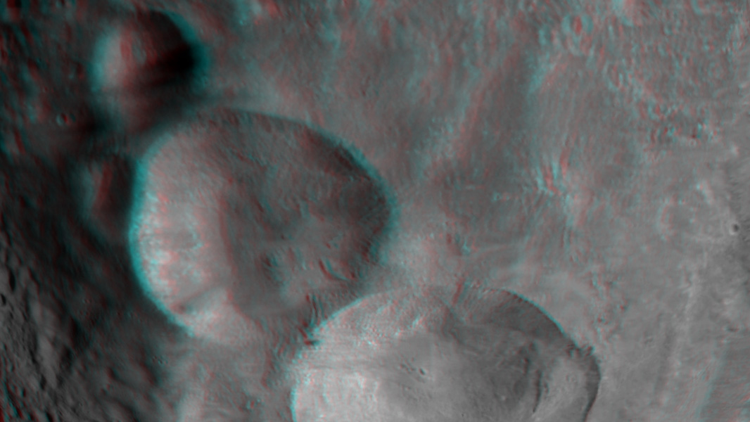 "This anaglyph shows the topography of Vesta's ""Snowman"" craters on asteroid Vesta. The bottom crater is named Marcia, the middle crater, Calpurnia, and the top crater, Minucia. You need 3-D glasses to view this image."