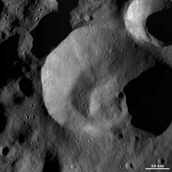 This image from NASA's Dawn spacecraft shows Caparronia crater on asteroid Vesta, an unusually shaped, irregular rim that is sharp and fresh in some areas and more rounded and degraded in others.