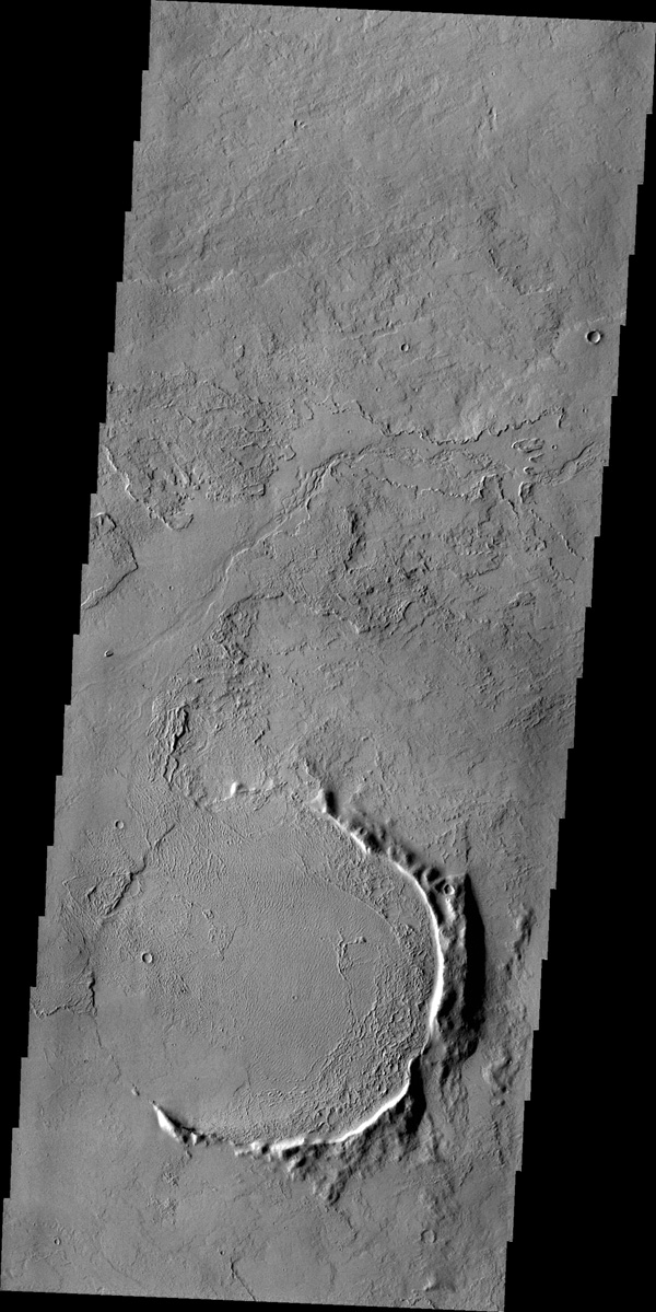 Only part of the rim of an unnamed crater remains visible above the lava flows in this region of Tharsis. This image is from NASA's 2001 Mars Odyssey spacecraft.