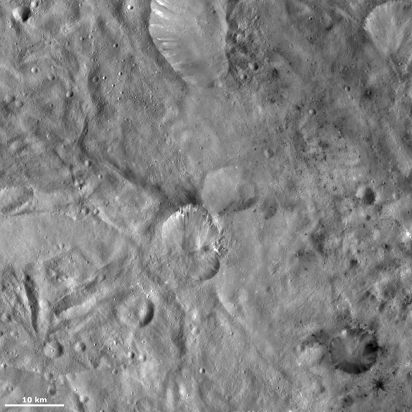 This image from NASA's Dawn spacecraft of asteroid Vesta shows Helena crater, which is the crater that resembles the shape of a butterfly's wings (center), and Laelia crater, which is the crater (bottom right).