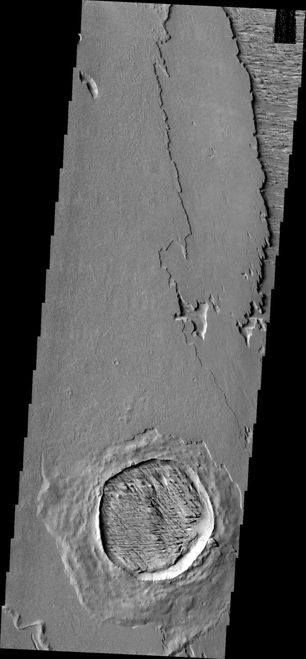 The crater in this image captured by NASA's 2001 Mars Odyssey spacecraft has not only been filled by wind-blown material, but that material has been eroded into the two directions of winnowing by continued wind action.
