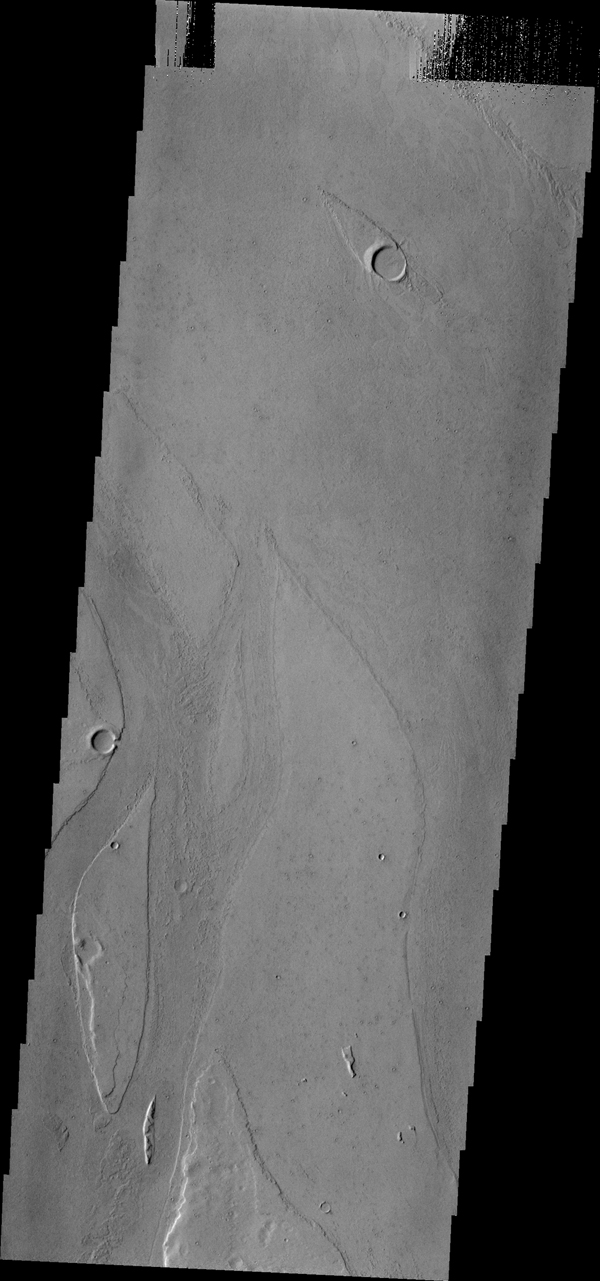 Marte Vallis, located in Amazonis Planitia, broad and shallow, is illustrated by the streamlined islands at the top and bottom of this image from NASA's 2001 Mars Odyssey spacecraft.