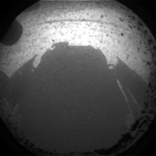 "This is the first image taken by NASA's Curiosity rover, which landed on Mars the evening of Aug. 5 PDT (morning of Aug. 6 EDT). It was taken through a ""fisheye"" wide-angle lens on one of the rover's front left Hazard-Avoidance cameras."