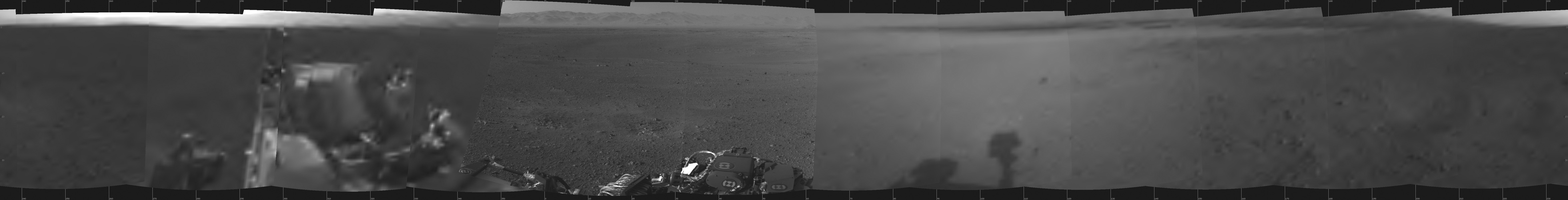 This is the first 360-degree panoramic view from NASA's Curiosity rover, taken with the Navigation cameras. Mount Sharp is to the right, and the north Gale Crater rim can be seen at center. The rover's body is in the foreground.