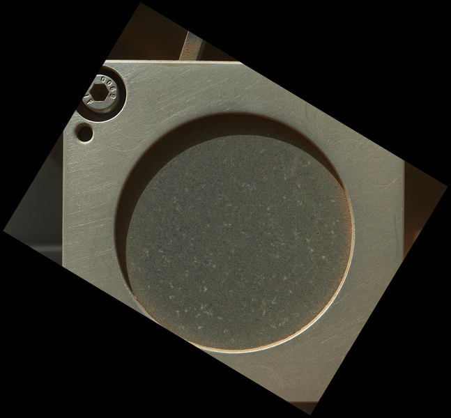 This image taken by the MAHLI camera shows a sample of basaltic rock from a lava flow in New Mexico serves as a calibration target carried on the front of NASA's Mars rover Curiosity for the rover's Canadian-made APXS instrument.