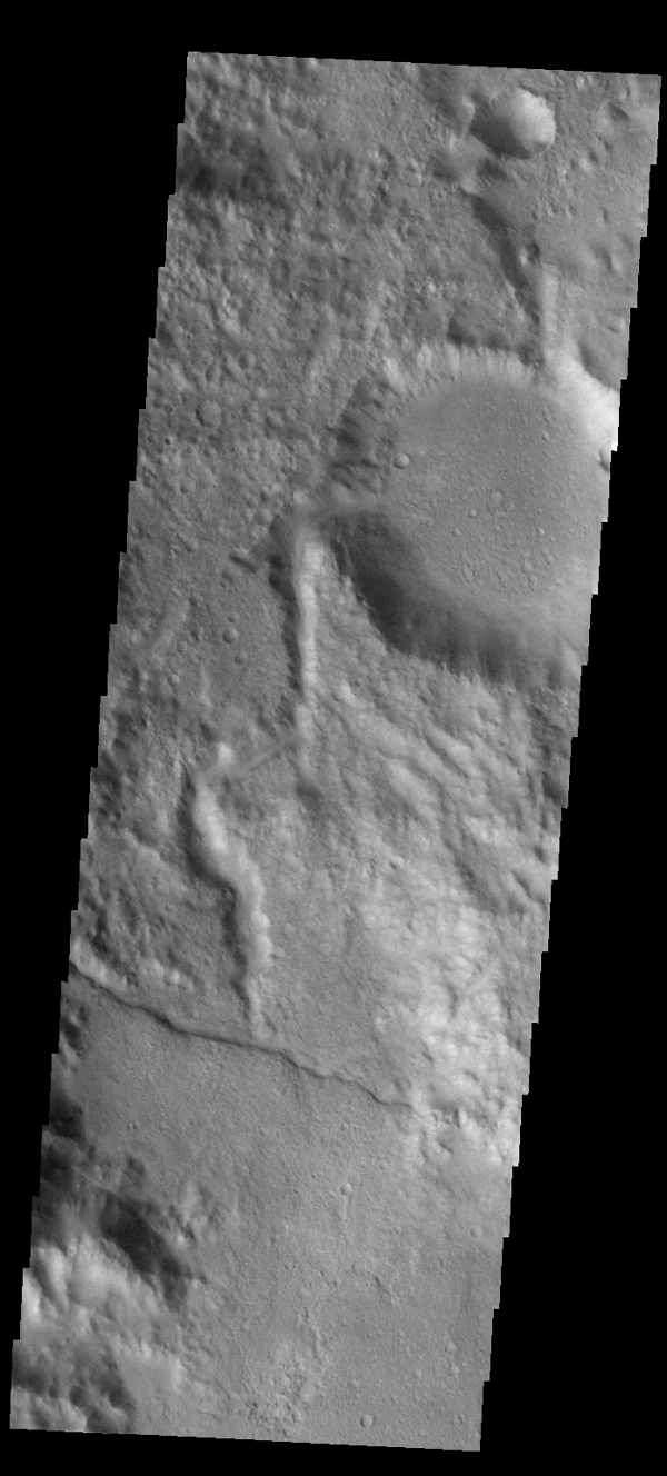 This image captured by NASA's 2001 Mars Odyssey spacecraft shows a channel entering a crater in the region called Libya Montes.